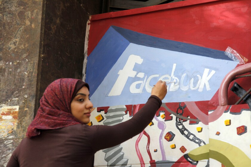 An art student paints the Facebook logo on a mural commemorating the 2011 uprising against former Egyptian President Hosni Mubarak in Cairo. Facebook says Egyptian authorities have shut down a program that was providing free basic Internet service to more than 3 million users in the country.