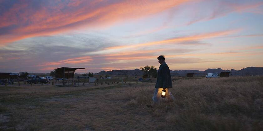 "A distant shot of Frances McDormand at sunset in ""Nomadland"""
