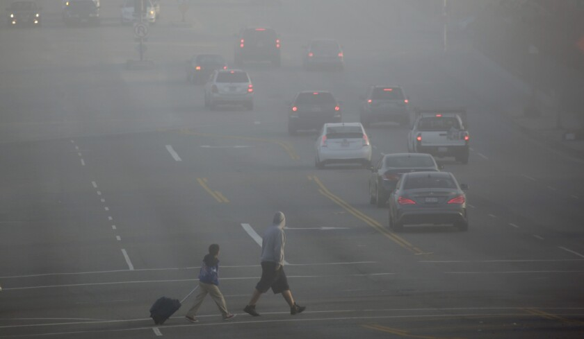 Residents in Boyle Heights navigate dense fog early Wednesday.