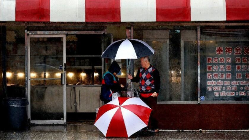 A vendor sells umbrellas on Broadway in Chinatown as a storm passed through the area last week.