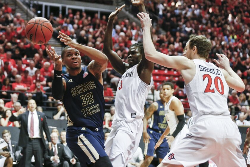 Georgia Tech forward Nick Jacobs loses the ball while being guarded San Diego State forward Angelo Chol and Matt Shrigley during the first half of an NCAA college basketball game in the men's NIT on Wednesday, March 23, 2016, in San Diego. (AP Photo/Lenny Ignelzi)