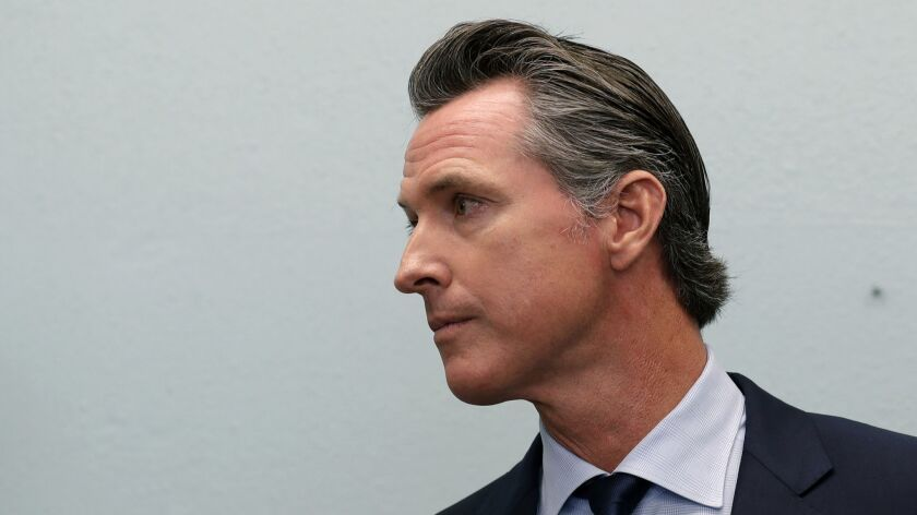 Governor-elect Gavin Newsom looks on during a news conference near the border on Nov. 29, 2018, in San Diego.