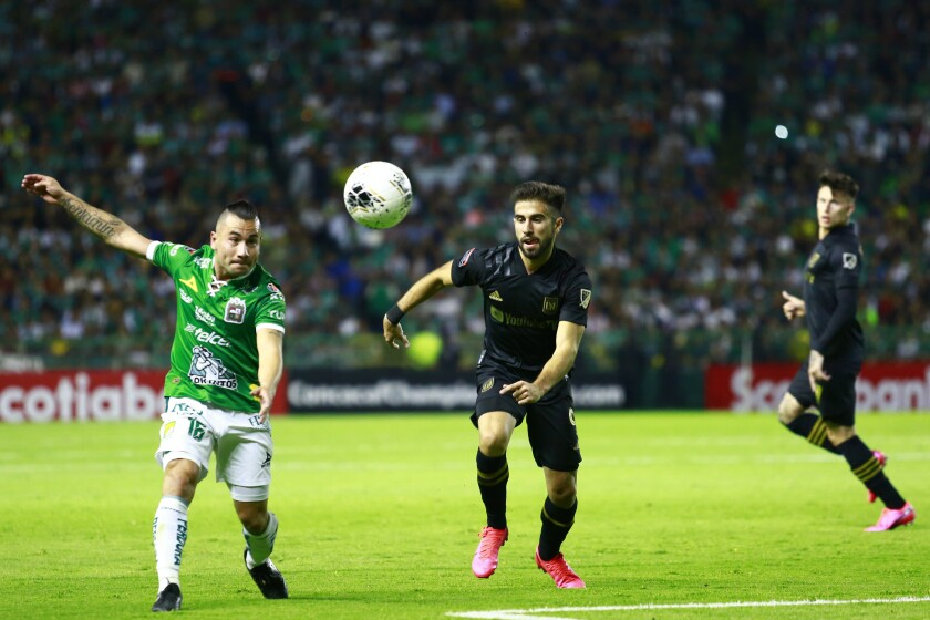 León's David Meneses, left, struggles for the ball with LAFC's Diego Rossi during the round of 16 match of the CONCACAF Champions League 2020 at Leon Stadium on Feb. 18 in León, Mexico.