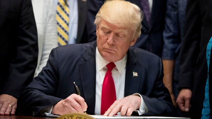 President Trump signs an executive order in the Roosevelt Room of the White House on Wednesday. Hours after officials said he was considering an order to leave NAFTA, he told Mexico and Canada the U.S. will stay put.