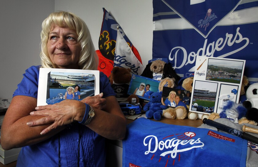 Longtime Dodgers fan Lois Peralta holds a photo of her and her daughter, Laurie Peralta, taken on their 30th consecutive opening day in 2010. Last August, driving home from a game, Laurie, 41, died in a crash. She was Lois' only child; Dodger Stadium, capacity 56,000, was the special place they went to be alone together.