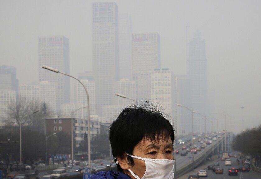 FILE - In this Dec. 20, 2015 file photo, a woman wearing a mask for protection against pollution walks on a pedestrian overhead bridge as office buildings in Central Business District of Beijing are shrouded with smog. China's far-reaching efforts to control the spread of the new coronavirus have shuttered factories, emptied airports and resulted in a steep drop in carbon emissions and other pollutants. However, analysts caution that the dip in pollution is likely temporary. (AP Photo/Andy Wong, File)