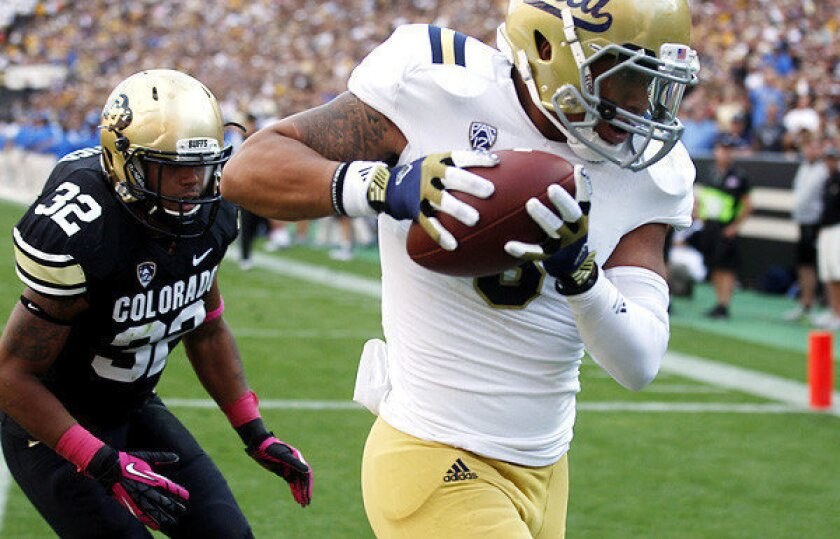 UCLA receiver Darius Bell snags a 17-yard touchdown pass in front of Colorado linebacker Paul Vigo in the second quarter Saturday.