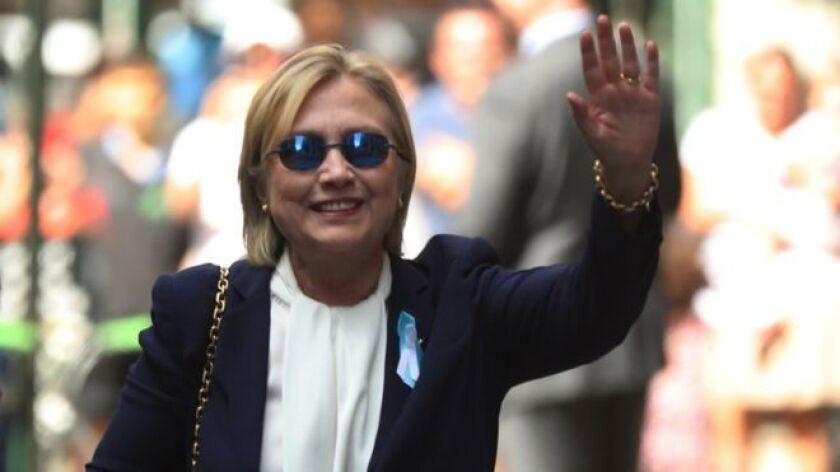 Clinton saluda a los fotógrafos al salir de la casa de su hija en Nueva York.