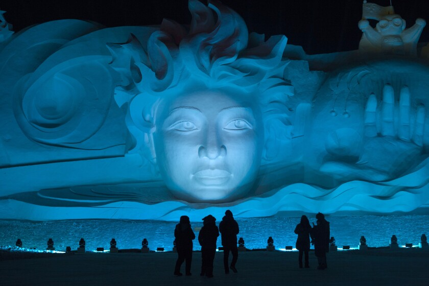 Tourists visit the Harbin International Snow Sculpture Art Expo at Harbin Sun Island park.