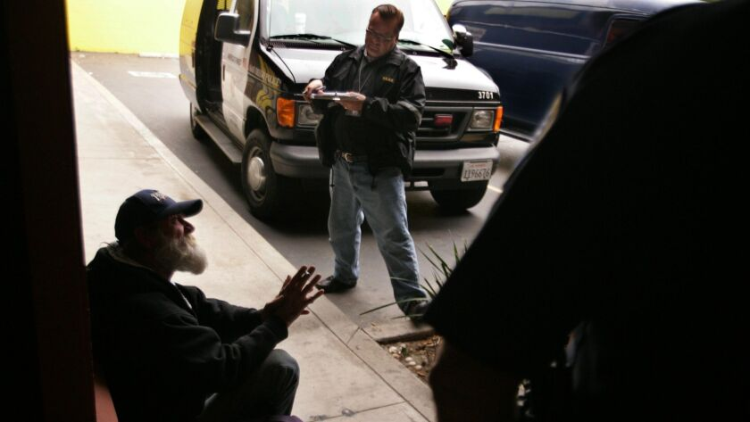 In this 2008 file photo, Greg Whitford, center, a member of the Homeless Response Team and a city of San Diego Psychiatric Emergency Response Team (PERT) clinician, speaks with a homeless man on Garnet Avenue in Pacific Beach.