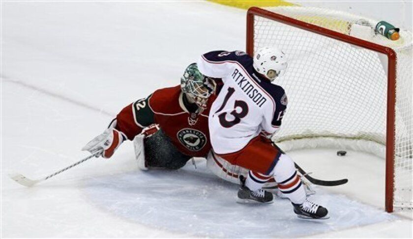 Columbus Blue Jackets right wing Cam Atkinson (13) scores the game-winning goal on Minnesota Wild goalie Niklas Backstrom (32), of Finland, during a shootout of an NHL hockey game in St. Paul, Minn., Saturday, April 13, 2013. The Blue Jackets defeated the Wild 3-2. (AP Photo/Ann Heisenfelt)