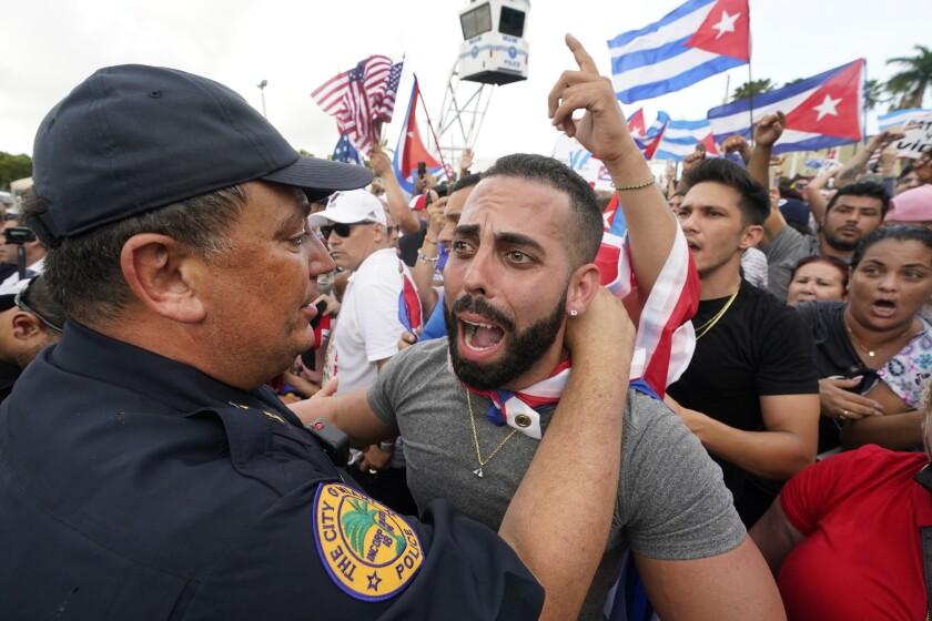 Foto tomada el 14 de julio del 2021 del jefe policial de Miami Art Acevedo (izq) abrazando a un manifestante que protestaba contra el gobiero cubano, en La Pequeña Habana, en Miami. (Foto AP/Wilfredo Lee, File)