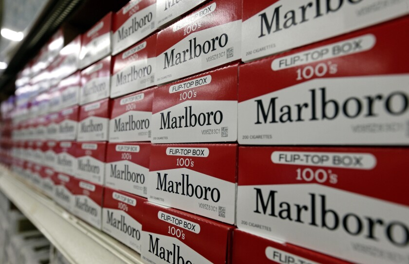 FILE- This June 14, 2018, file photo shows cartons of Marlboro cigarettes on the shelves at JR outlet in Burlington, N.C. Philip Morris International is moving its corporate headquarters from New York to Connecticut. The company said Tuesday, June 22, 2021, the relocation will bring about 200 new jobs to Connecticut. (AP Photo/Gerry Broome, File)