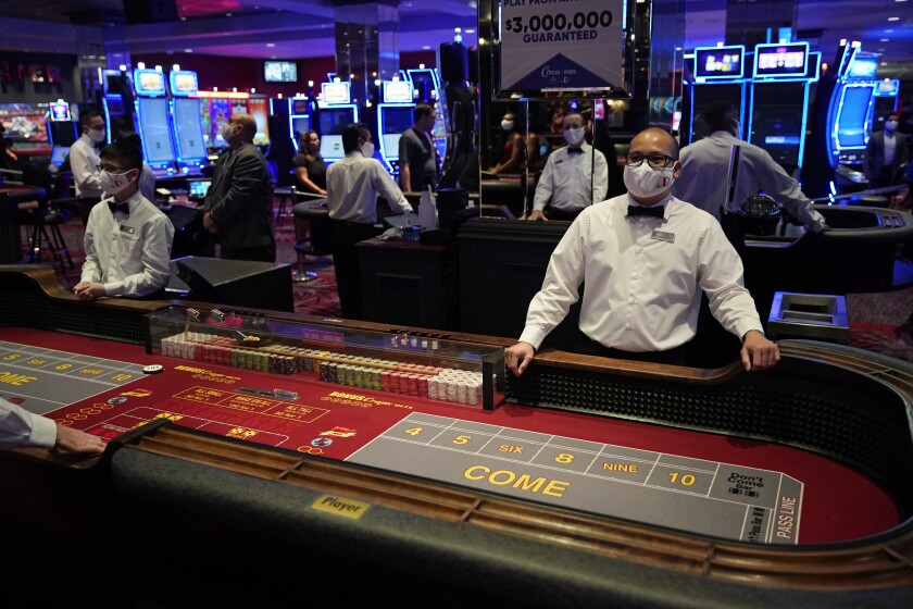 Dealers in masks wait for customers at the D Las Vegas hotel and casino.