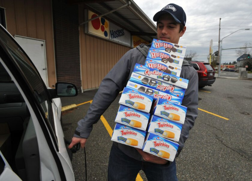 Andy Wagar loads Twinkies, Ho-Ho's and cupcakes into a van outside the Wonder Bakery Thrift Shop in Bellingham, Wash.