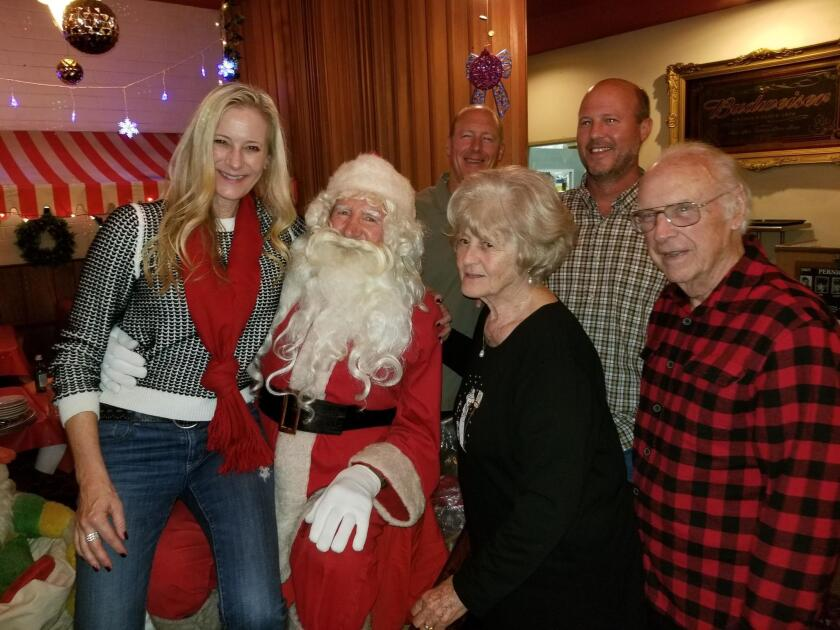 The Darrock family in 2018 poses with Santa John Pernicano, who they've been coming to see every holiday season for decades at Pernicano's Family Restaurant in Pacific Beach.