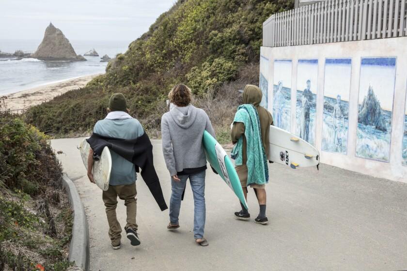 Surfers make their way to Martins Beach