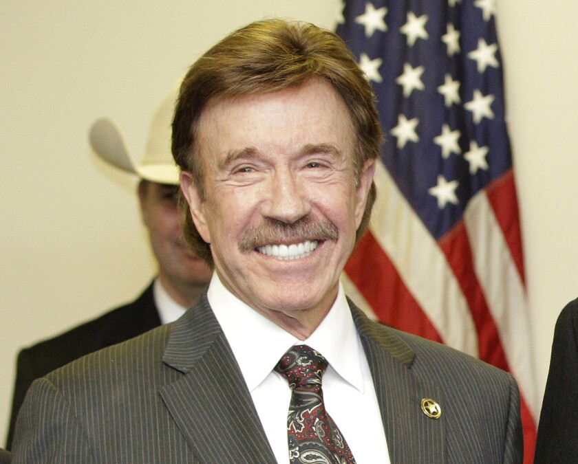 """FILE - In this Dec. 2, 2010, file photo, actor Chuck Norris stands following a ceremony in Garland, Texas. Norris' manager says the """"Walker, Texas Ranger"""" star was not present at last week's deadly riot at the U.S. Capitol. A photo of a man resembling Norris apparently with a member of the mob began trending online. (AP Photo/Tony Gutierrez, File)"""