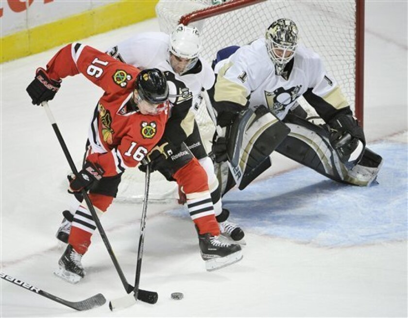 Chicago Blackhawks center Marcus Kruger, left, of Sweden, tries to score as Pittsburgh Penguins defenseman Brian Strait, center, and goalie Brent Johnson defend during the first period of a preseason NHL hockey game, Friday, Sept. 30, 2011, in Chicago. (AP Photo/Brian Kersey)