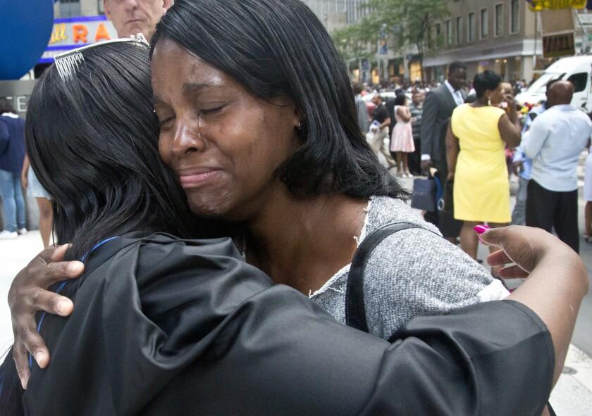 En esta imagen, tomada el 9 de junio de2015, Candie Hailey (derecha), llora mientras abraza a su hermana Chyna tras su graduación universitaria en Nueva York. Candie pasó dos años y un tercio en aislamiento en el penal de Rikers. (Foto AP /Bebeto Matthews)