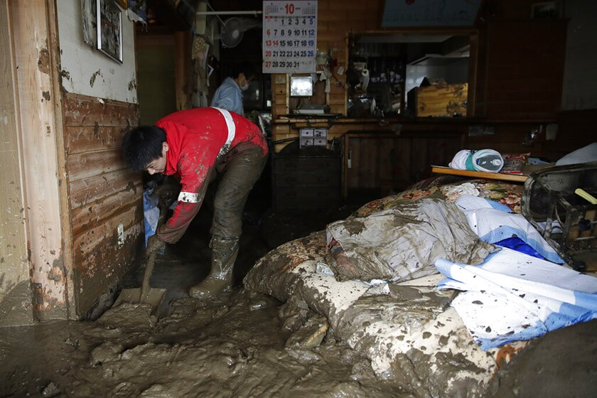 Yoshiki Yoshimura, 17, cleans his home Oct. 15 in Nagano, Japan. The number of deaths tied to Typhoon Hagibis climbed to 53 and was expected to rise.
