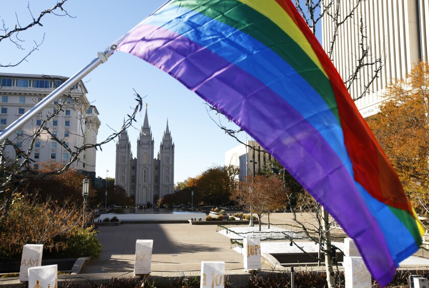 A pride flag flies in front of the Salt Lake Temple in Salt Lake City during a protest by Mormons who resigned en masse Saturday from the church.