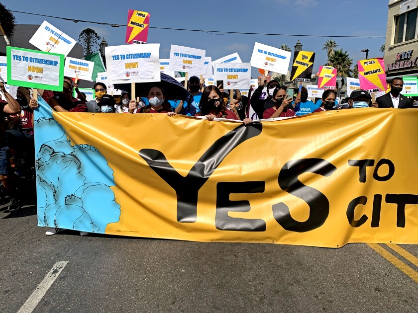 """Demonstrators hold """"Yes to citizenship"""" signs at a march"""