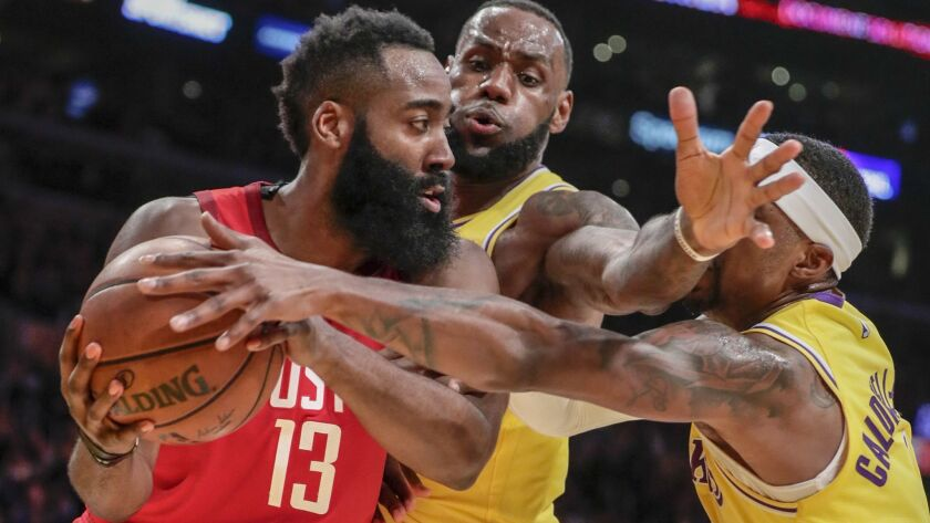 Houston Rockets guard James Harden is defended tightly by Lakers forward LeBron James and guard Kentavious Caldwell-Pope during second half on Thursday at Staples Center.