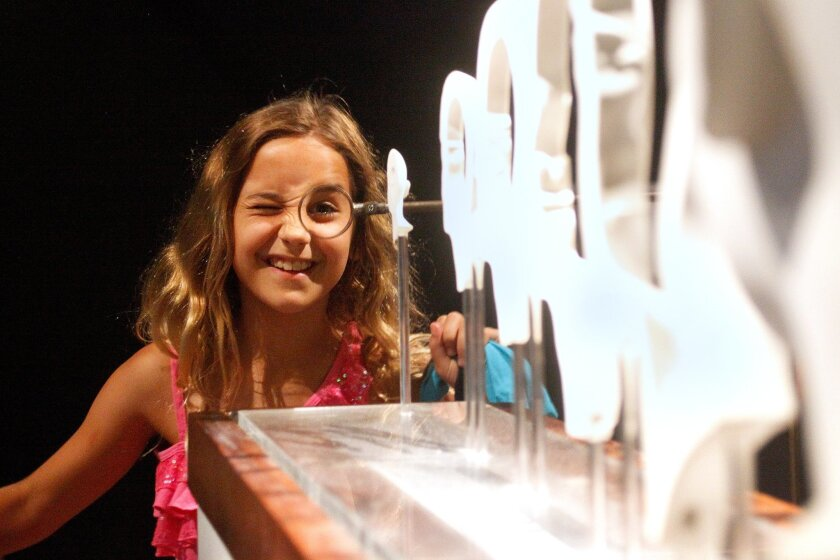 Cami Fisher, 9, of Point Loma looks into The Hurwitz Singularity sculpture at the new Illusions exhibit at the Reuben H. Fleet Science Center. Misael Virgen/ UT San Diego