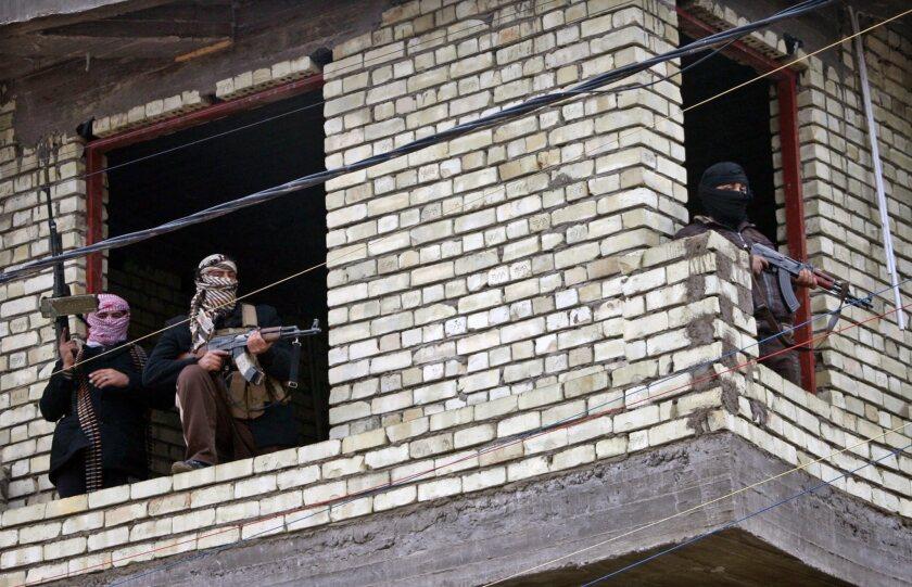 Masked Sunni gunmen are seen taking position in Fallujah, Iraq.
