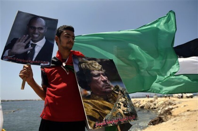 A Palestinian youth holds posters of Saif al-Islam Gadhafi, left, and his father the Libyan leader Moammar Gadhafi, during a rally to support a Libyan ship making its way towards Gaza in the latest attempt to thwart an Israeli naval blockade, in Gaza City, Wednesday, July 14, 2010. Flanked by Israe