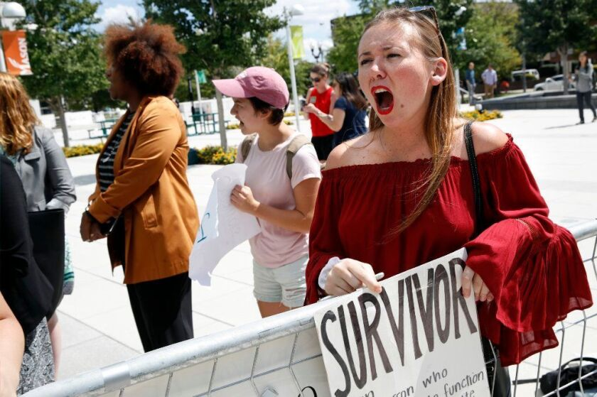 Meghan Downey, 22, a recent graduate from the College of William & Mary, reacts outside an auditorium after Education Secretary Betsy DeVos spoke about proposed changes to Title IX, Thursday, Sept. 7, 2017, at George Mason University Arlington, Va.
