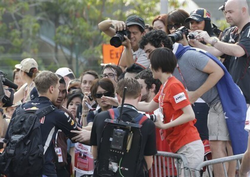 Red Bull Formula One driver Sebastian Vettel, left,of Germany signs autographs for fans as he arrives for the third practice session for the Singapore Formula One Grand Prix on the Marina Bay City Circuit in Singapore, Saturday, Sept. 22, 2012. (AP Photo/Dita Alangkara)