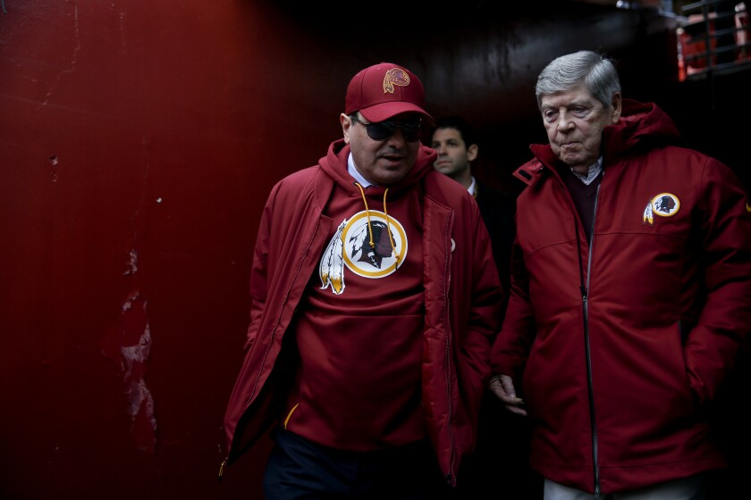 Washington Redskins owner Dan Snyder, left, walks onto the field before a game.