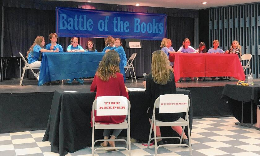 Teams from Eastbluff, left, and Newport Heights elementary schools compete Wednesday in the final round of the Newport-Mesa Unified School District's first Battle of the Books tournament. The Eastbluff group won the test of knowledge of books the students had read since September.