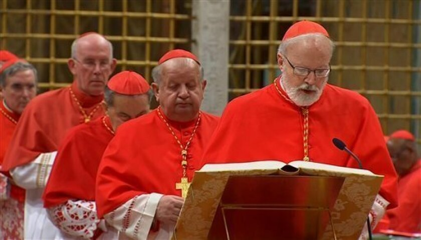 In this image made from video provided by Vatican CTV television, US Cardinal Sean Patrick O'Malley, right, takes an oath of secrecy inside the Sistine Chapel, at the Vatican, Tuesday, March 12, 2013, before the start of the conclave to elect the 266th Roman Catholic Church pope. Behind O'Malley ar