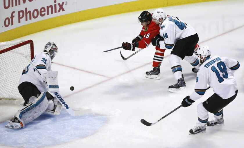 San Jose Sharks goalie Martin Jones (31) makes a save on a shot by Chicago Blackhawks center Jonathan Toews (19) as Marc-Edouard Vlasic (44) and Joe Thornton defend, during the first period of an NHL hockey game Tuesday, Feb. 9, 2016, in Chicago. (AP Photo/Charles Rex Arbogast)