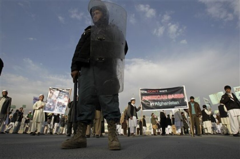 An Afghani police force stands guard as protestors shout anti America slogans during a peaceful protest in Kabul, Afghanistan, Thursday, April 7, 2011. Clerics at a peaceful protest of about 300 people in Kabul say a U.S. pastor who burned a Quran should be prosecuted and Americans should withdraw from Afghanistan. (AP Photo/Kamran Jebreili)