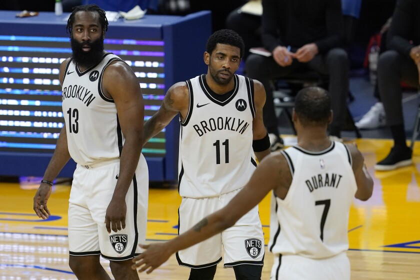 Brooklyn Nets guard Kyrie Irving gathers with guard James Harden and forward Kevin Durant.