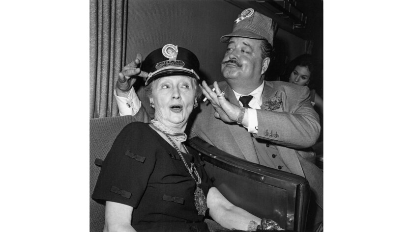 """Aug. 9, 1962: Jackie Gleason with train """"conductor"""" -- Los Angeles Times Hollywood columnist Hedda Hopper -- during his $80,000 cross-country excursion."""