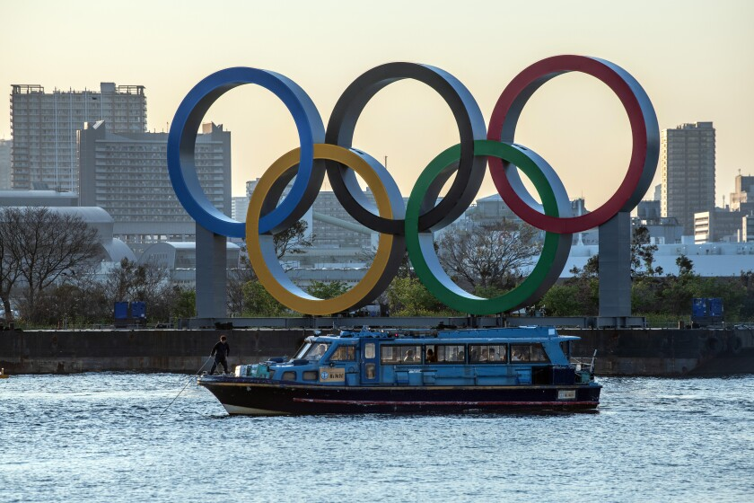 A man pulls up the anchor on a pleasure boat moored next to the Tokyo 2020 Olympic Rings.