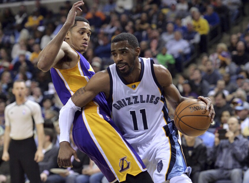Grizzlies guard Mike Conley (11) drives against Lakers guard Jordan Clarkson during the second half on Wednesday.