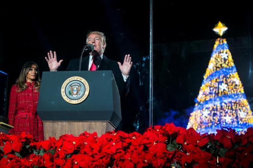 El presidente de los estados Unidos, Donald Trump (c), habla junto a la primera dama, Melania Trump (i), durante la ceremonia de iluminación del Árbol Nacional de Navidad. EFE/POOL