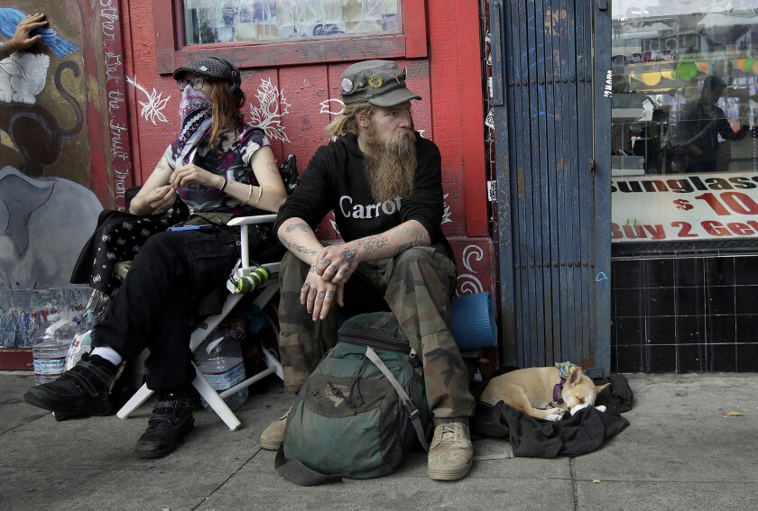 In this Oct. 1, 2018 photo, Stormy Nichole Day, left, sits on a sidewalk on Haight Street with Nord (last name not given) and his dog Hobo while interviewed about being homeless in San Francisco.