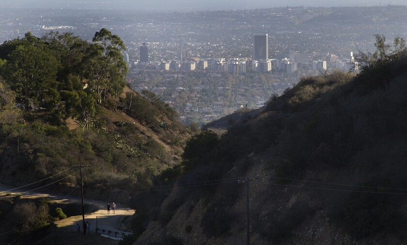 Green vegetation is mixed with dry chaparral as hikers walk along a dirt trail in Runyon Canyon Park on Sept. 28, 2015, in Los Angeles. With tinder dry brush and Santa Ana winds possible, the Southland is at risk of big brushfires.