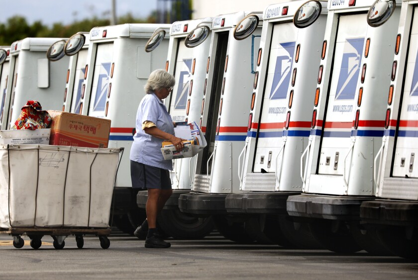 A mail carrier loads a truck for delivery at a U.S. post office in Torrance.
