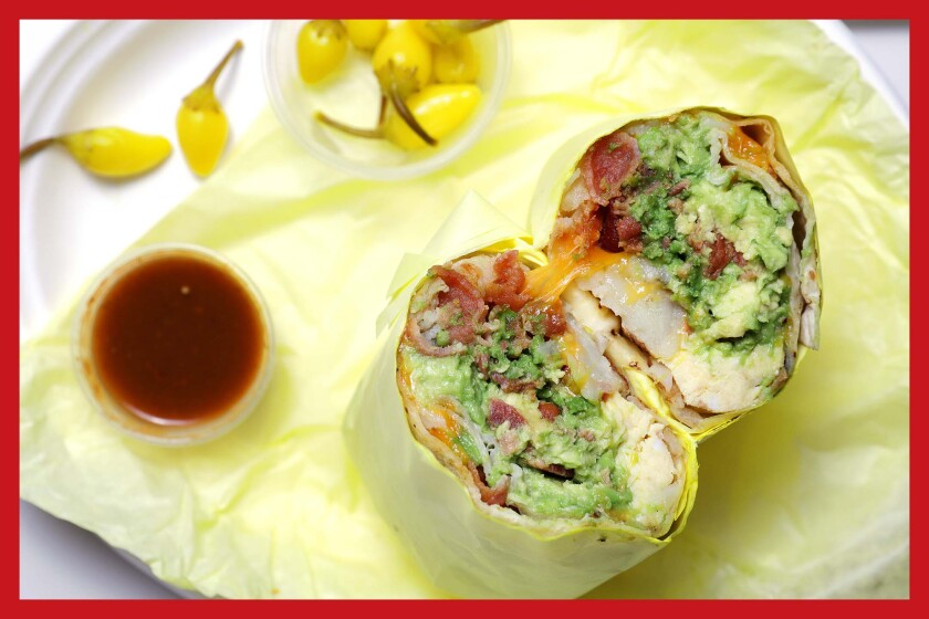 An avocado and bacon breakfast burrito on yellow paper flanked by cups with peppers and sauce