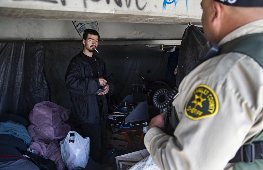 L.A. County sheriff's Deputy Michael Tadrous of the Homeless Outreach Services Team talks with Shawn Troncozo, 24, about how to prevent the spread of the coronavirus near the San Gabriel River.