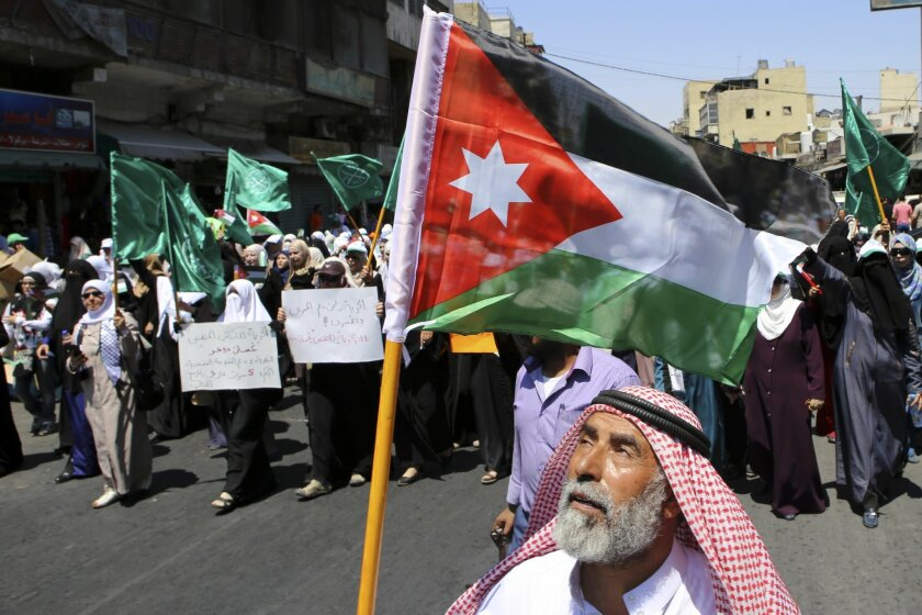 FILE -- In this July 31, 2015 file photo, a Jordanian protester carries the national flag during a rally by the Muslim Brotherhood, in Amman, Jordan. A spokesman says Jordan's branch of the Muslim Brotherhood has formally cut ties with the region-wide movement based in Egypt. The decision is the la