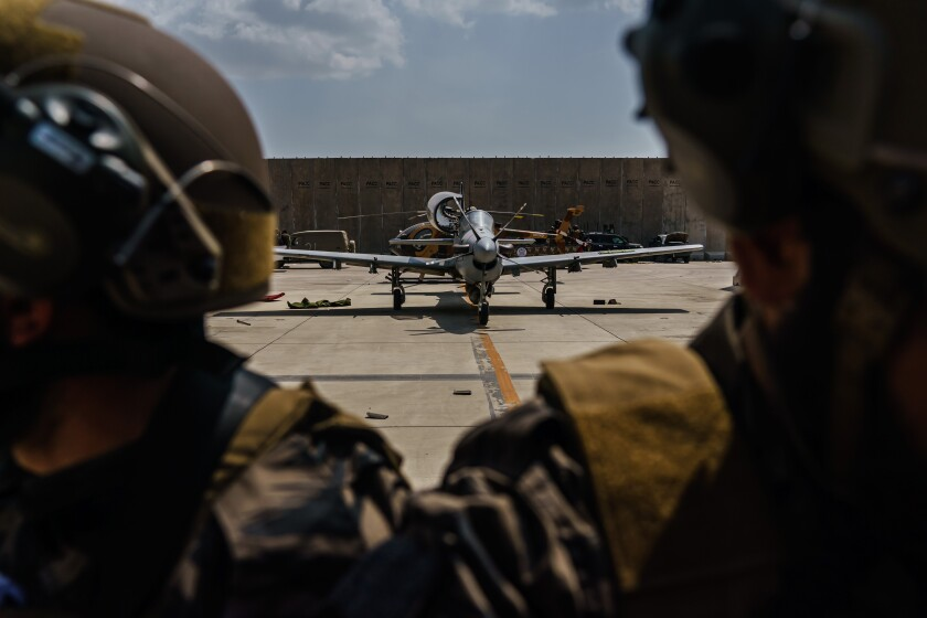 KABUL, AFGHANISTAN -- AUGUST 31, 2021: Taliban fighters stand ready in front of the Afghan A-29 Super Tucano, as the militant group secure the Hamid Karzai International Airport, in the wake of the American forces completing their withdrawal from the country in Kabul, Afghanistan, Tuesday, Aug. 31, 2021. (MARCUS YAM / LOS ANGELES TIMES)